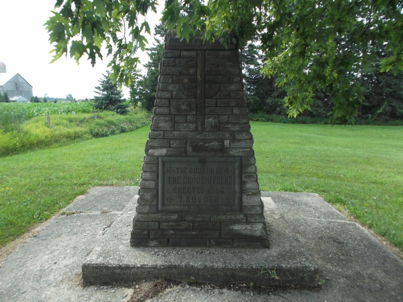Picture of a cement plaque on the cairn in the cemetery