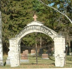 Picture of the stone and iron gate to the cemetery. There is an arch over the gate.