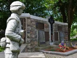 Picture of the cenotaph with a statue of a soldier standing to the side of it.