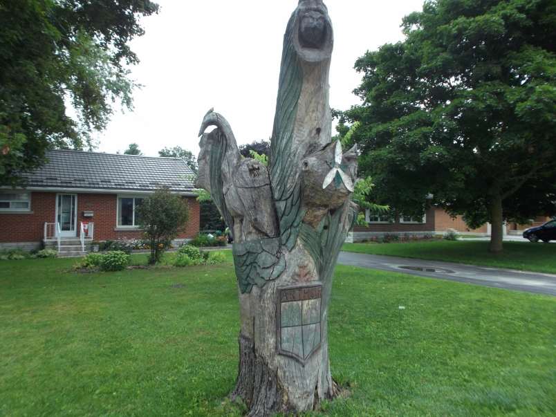 Picture of a tree sculpture showing crest of Arthur, heron, own, coyote