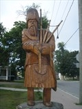 A tree sculpture in the shape of a Scottish piper.